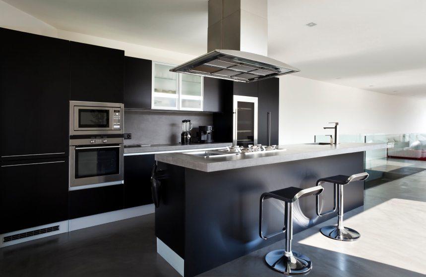 Modernt kök med svart mörkt betong golv